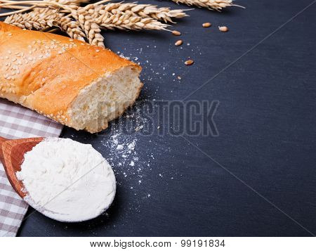 Flour, Bread And Wheat Ears On Black Background