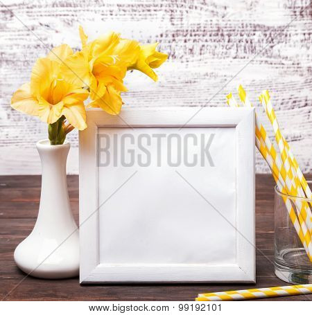 White Empty Frame With Place For Text Or Picture On The Table With Yellow Flowers In A Vase