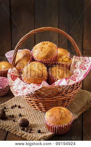 Fruit muffins with nutmeg and allspice in a wicker basket on a wooden background