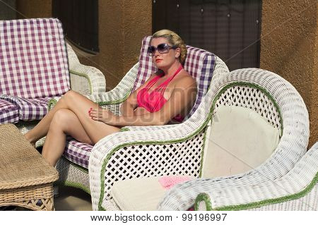 The Beautiful Woman In A Red Bathing Suit Sits In A Chair