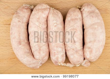 Raw Chicken Sausages On Wooden Board