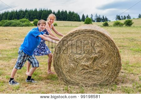 Mother And Son Rolling Hay Bale In Countryside