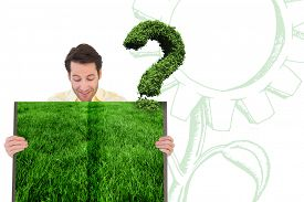 stock photo of punctuation marks  - Man holding lawn book against question mark made of leaves - JPG