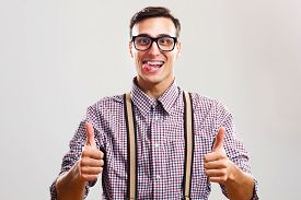 pic of sticking out tongue  - Happy nerdy man sticking out tongue and  showing thumb up - JPG