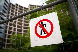 picture of no entry  - No entry sign on the fence in contruction site with house under construction and green trees in the background - JPG