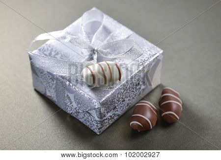 Close up of a gift pack wrapped in a silver paper and date-chocolates.