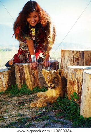 young woman with ornamental dress and gold jewel playing with lion cub in nature, with wolf fur.
