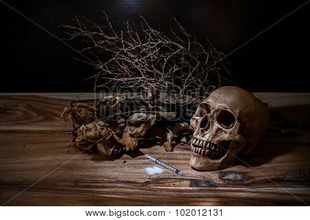 Still Life Narcotic Syringe With The Skull On Wooden Table.