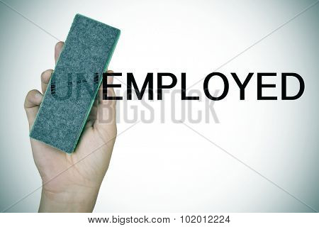 closeup of the hand of a young man deleting the prefix UN in the word unemployed with an eraser to convert it in the word employed