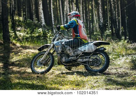 Enduro racer is riding through woods