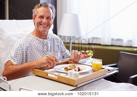 Male Patient In Hospital Bed Eating Meal From Tray