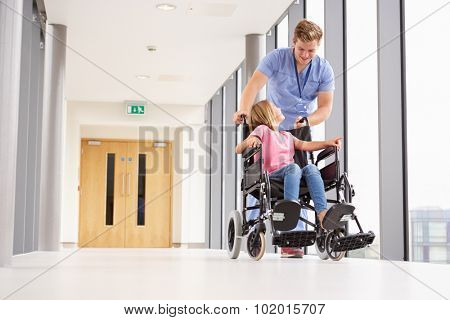 Nurse Pushing Girl In Wheelchair Along Corridor