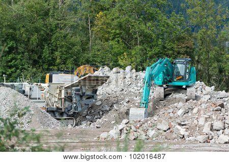stone breaker and shovel digger on demolition site