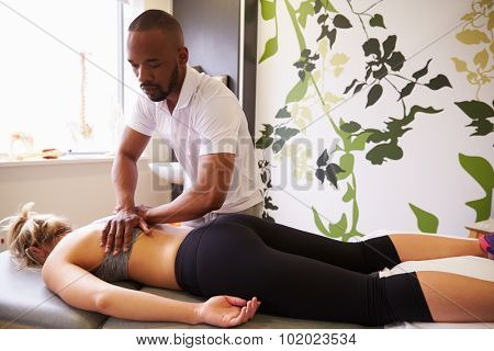 Physiotherapist Giving Female Patient Massage In Hospital