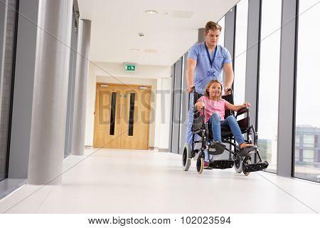 Nurse Pushing Girl In Wheelchair Along Corridor