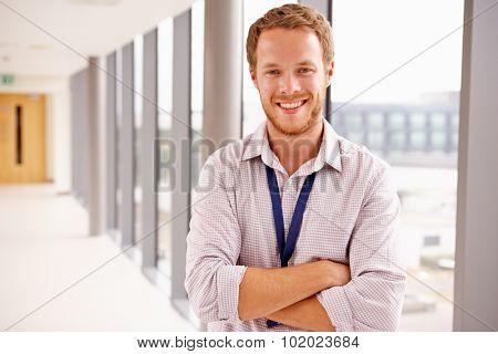 Portrait Of Male Doctor Standing In Hospital Corridor