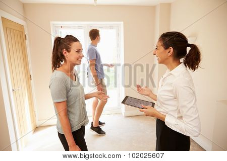 Couple viewing a home interior with an estate agent