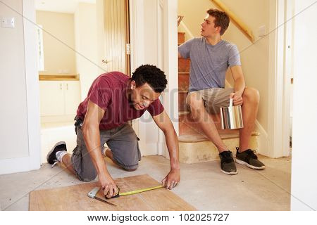 Two men decorating the hallway of a house