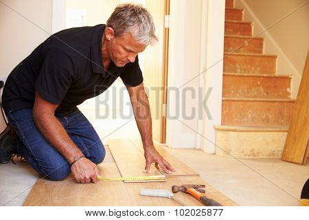 Man laying wood panel flooring during a house refurbishment