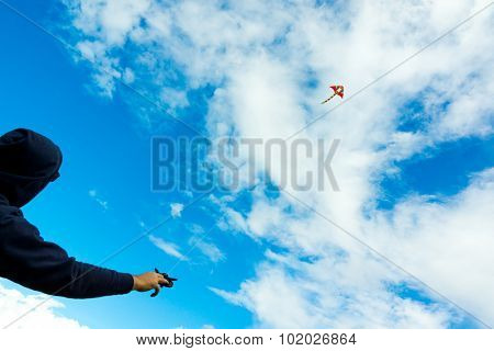 Man holding kite in the cloudy sky. Focus to the kite