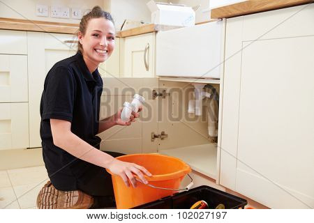Female plumber holding a u-bend pipe for a kitchen sink