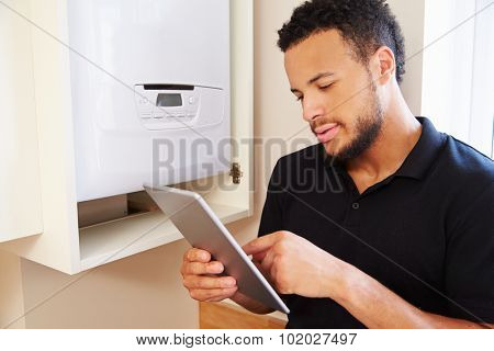 Technician servicing boiler using tablet computer