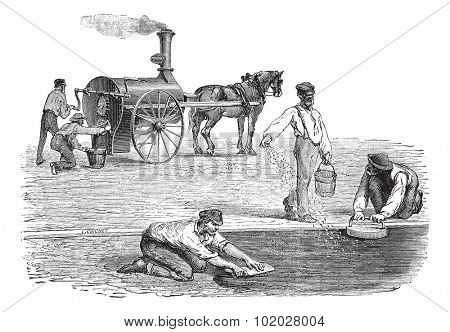 Old engraved illustration of road workers making pavement with the help of steam engine. Industrial encyclopedia E.-O. Lami - 1875.