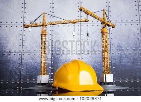 Building under construction with crane, on blueprints