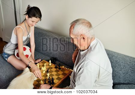 Smiling Granddaughter And Grandpa Playing Chess