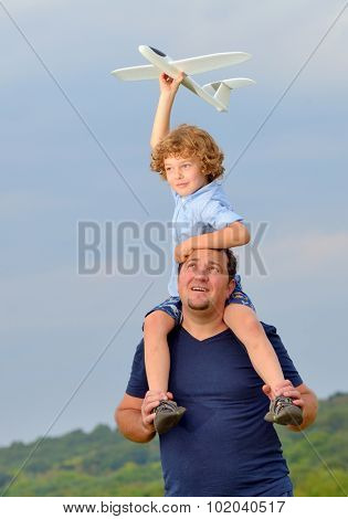 Father carrying son and his plane on shoulders