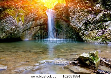 small waterfall on mountain river against sunshine in forest