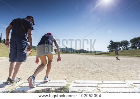Tourists Ready To Run At Olympia, Birthplace Of The Olympic Games, In Greece.