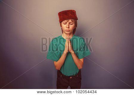 Muslim boy of ten years, skullcap, prayer on a gray background r