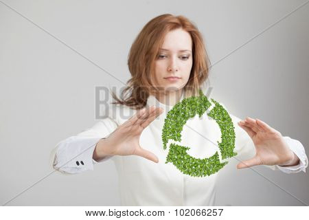 Young woman holding green recycle symbol in his hands