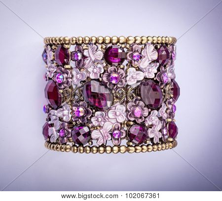 Beautiful bracelet with precious stones on color background.