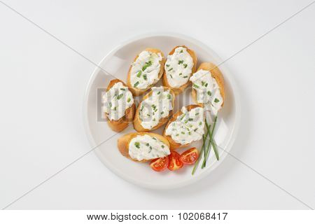 crunchy croutons with chives spread on white plate