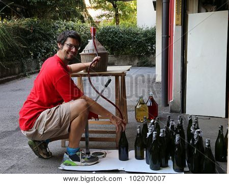 Young Man Smiling While Bottling The Wine At Home