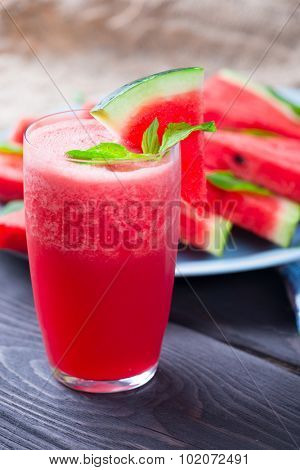 Watermelon drink in glass with slices of watermelon on wooden background