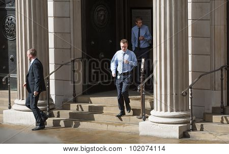 LONDON, UK - SEPTEMBER 17, 2015: Businessmen run out from the Bank of England doors