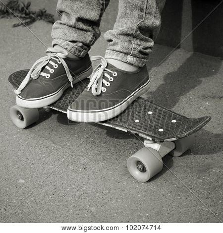 Feet In Jeans And Gumshoes On A Skateboard