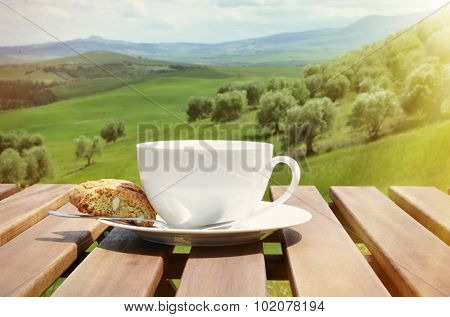Coffee and cantuccini on the wooden table against Tuscan landscape, Italy