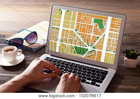 Laptop with map gps navigation application on wooden table in office