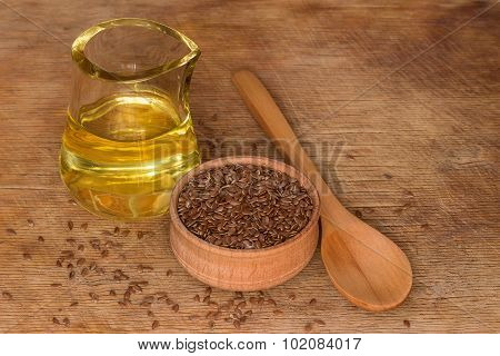 Flax Seeds With Oil On A Wooden Table.