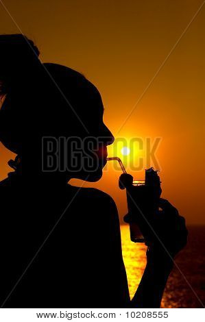 Sunset silhouette of a woman drinking a cocktail