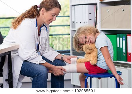 Female Doctor Bandaging The Leg From A Of Girl