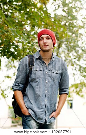 Handsome Young Man In A Red Cap Carrying A Backpack