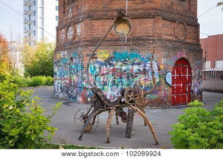 Izhevsk, Russia - September 16, 2015: Scrap Metal Modern Sculpture On The Street Of The Town With Gr