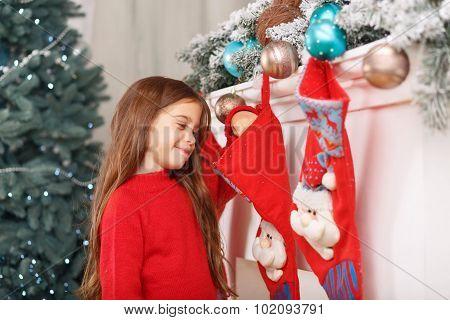 Little girl standing near fireplace