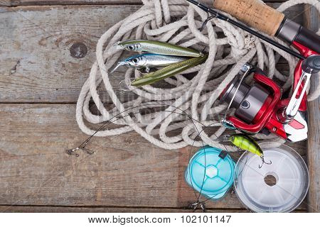 Fishing Tackles On Wooden Board With Rope