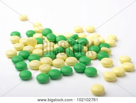 A Heap Of Green And Yellow Medicine Pills On White Surface.